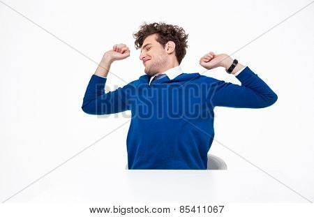 Happy businessman sitting at the table and stretching