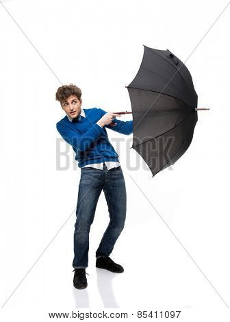 Handsome businessman standing with umbrella over white background