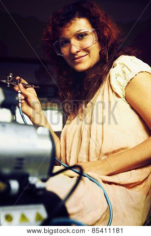 A young woman painting with airbrush equipment