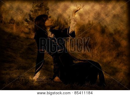 girl in historical costume sitting on a meadow with her hand in symbolic gesture raised and open tow