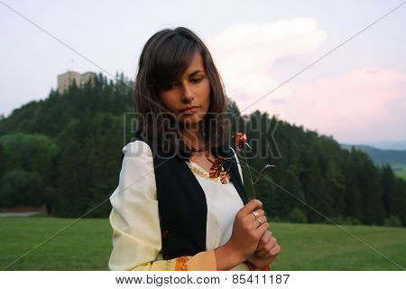 beautiful girl in historical costume in a wild meadow landscape holding a secretful romantic rose