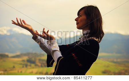 beautiful young woman with dark hair and a historical dress posing on a meadow in open lanscape wit