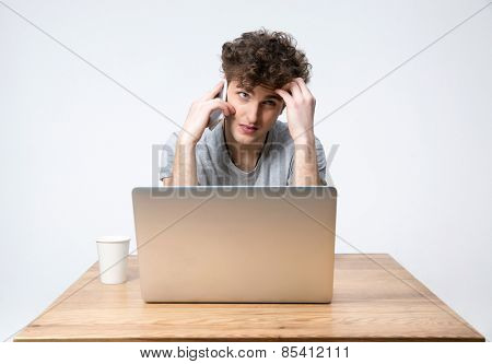Pensive young man sitting at the table with laptop and talking on the phone