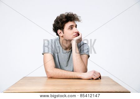 Pensive young man sitting at the table and looking away