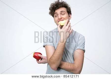 Young man holding apple and eating unhealthy donut