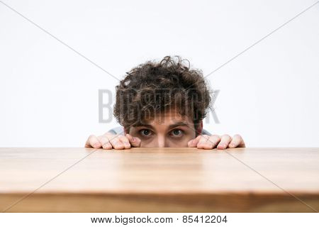 Young man with curly hair peeking from behind the desk