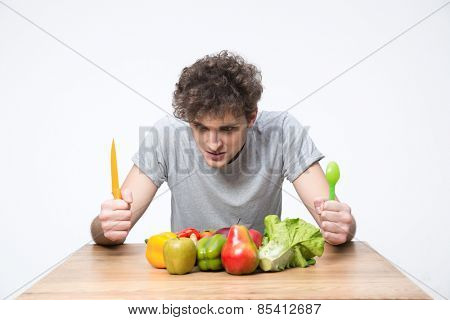 Hungry man sitting at the table with vegetables