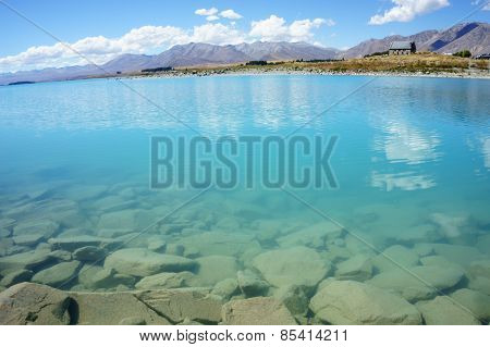 Natural turquoise Lake Tekapo and rocky edge New Zealand