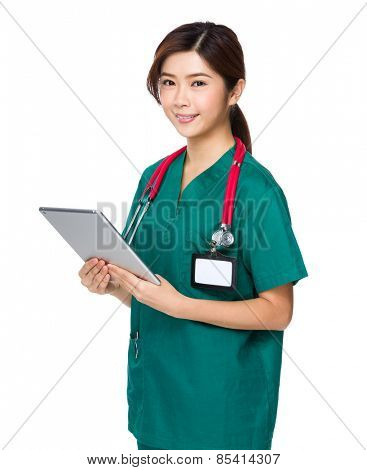 Young woman doctor in scrubs using tablet computer