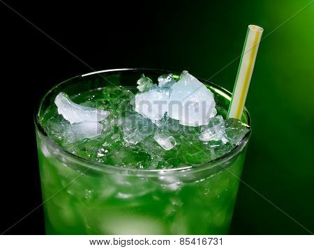 Green drink  with crushed ice on dark background. Top view.