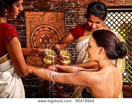 Woman having Ayurvedic spa treatment. Pouring milk.