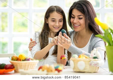 Mom and  daughter together painting Easter eggs