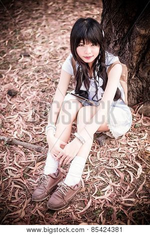 A Cute Asian Thai Girl Is Sitting With Her Knees Up Under The Tree With Her Tablet On The Laps In Au