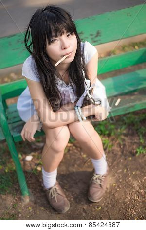 A Cute Asian Thai Girl Is Sitting On The Bench With A Stick In Her Mouth  And Making Eye Contact