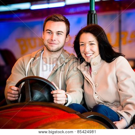 Young couple riding car in amusement park
