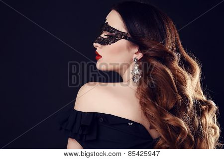 gorgeous woman with dark hair and blue eyes with lace mask on her face