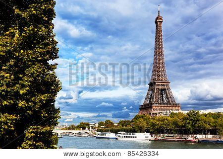 Eiffel Tower and Seine River, Paris, France. Unique perspective from behind trees next to tourist boats.