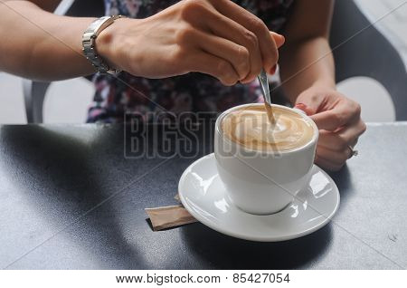 Hand stirring hot cappuccino coffee in cafe