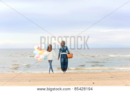 Mother And Daughter Together Holding Hands And Contemplating Seaside