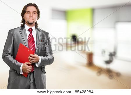 Businessman With Red Clipboard In Office