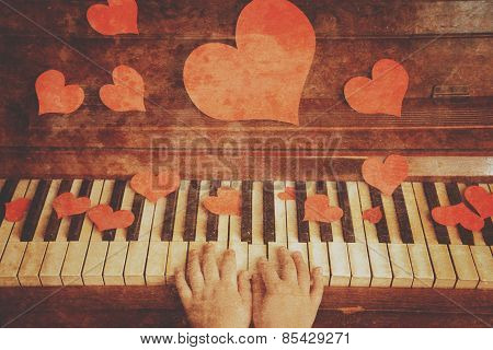 Child playing on a piano, vintage image