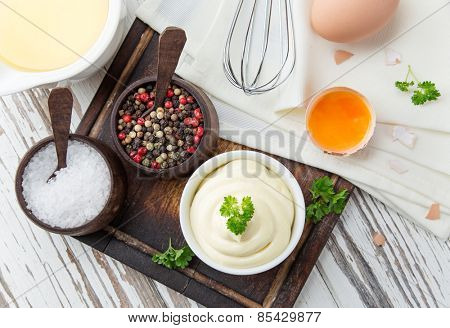 Mayonnaise in bowl on wooden table.