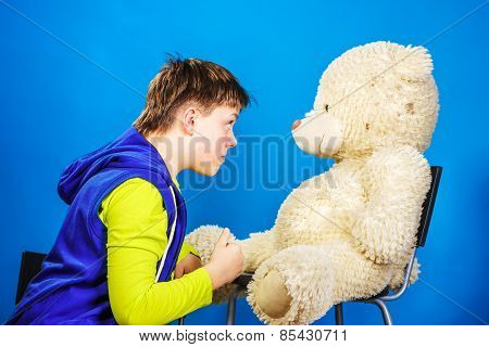 Teenage boy speaking with his old teddy-bear toy