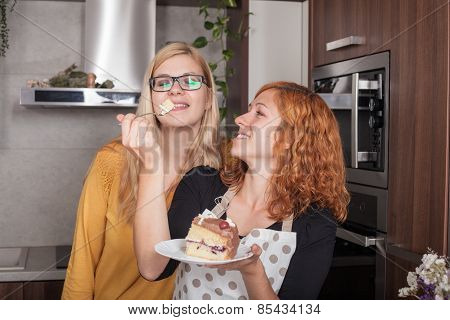 Happy Girlfriends Eating Cake In The Kitchen