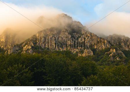 Rocky peaks at foggy sunrise, trekking path at Suva Planina mountain
