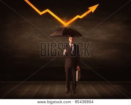 Businessman standing with umbrella keeping orange arrow concept on background