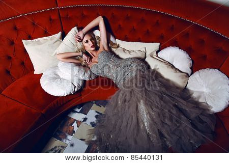 Gorgeous Woman With Blond Hair In Elegant Dress Lying On Red Divan