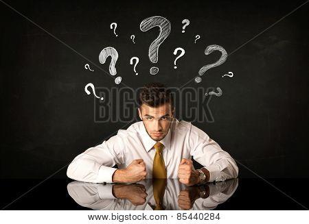 Depressed businessman sitting under question marks
