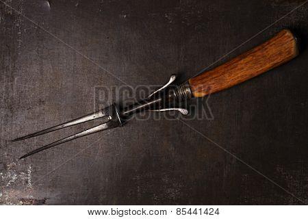 stylish vintage meat carving fork on metal backdrop