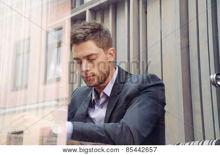 Attractive Businessman Using Device And Drinking Coffee In The City Cafe