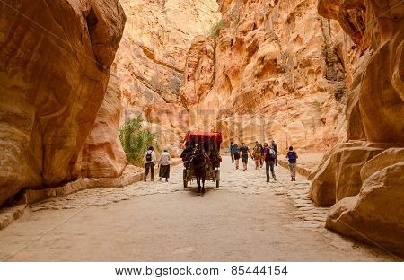 Tourists Ride In A Carriage And Go Through The Gorge In Petra, Jordan