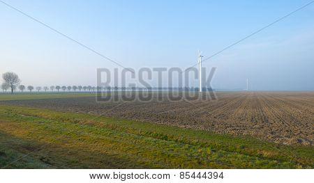 Wind turbine in a plowed field in winter