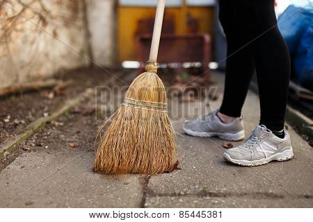 Woman Sweep Leaves And Soil Into Bin