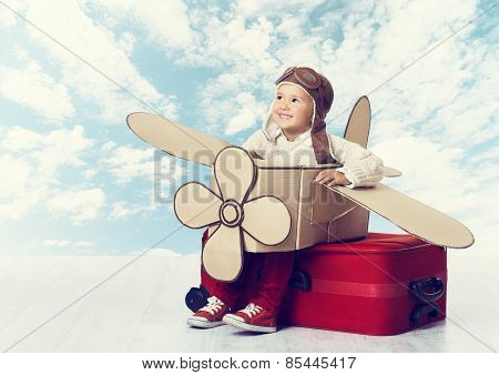Little Child Playing Airplane Pilot, Kid Traveler Flying In Aviator Helmet On Travel Suitcase