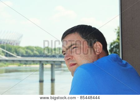 Side portrait low angle view of a man standing and looking ahead against a blue sky
