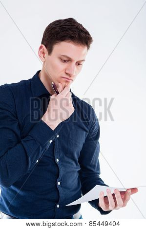 Businessman reading contract and holding pen to sign it