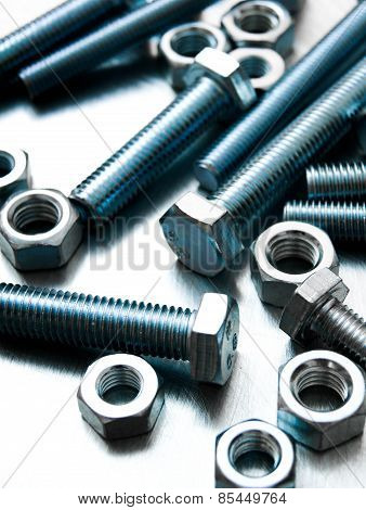 Nuts and bolts on scratched metal background.