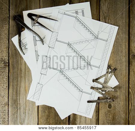 Many drawings for building and working tools on old wooden background.