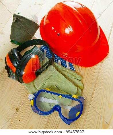 helmet, ear-phones, glasses protective and other tool on a wooden background.