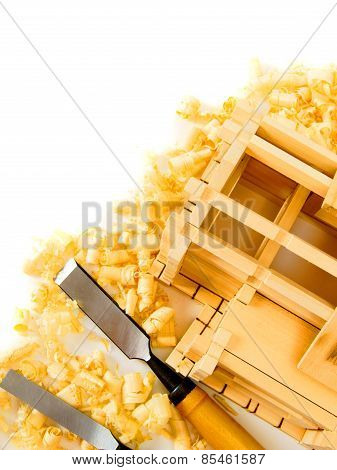 House construction. The wooden house, chisel and shaving on white background.