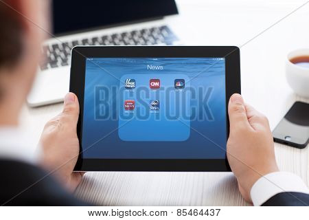 Businessman Holding Ipad With News App On The Screen