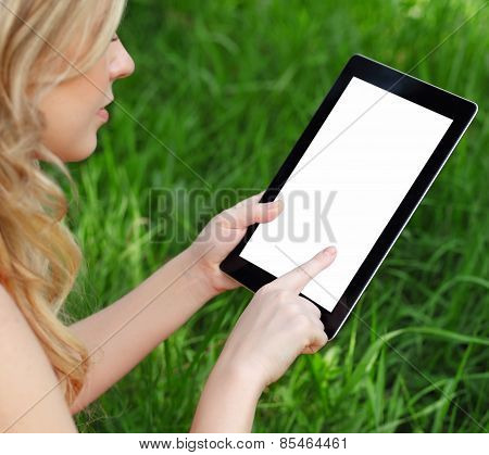 Girl Holds A Tablet On A Background Of Green Grass