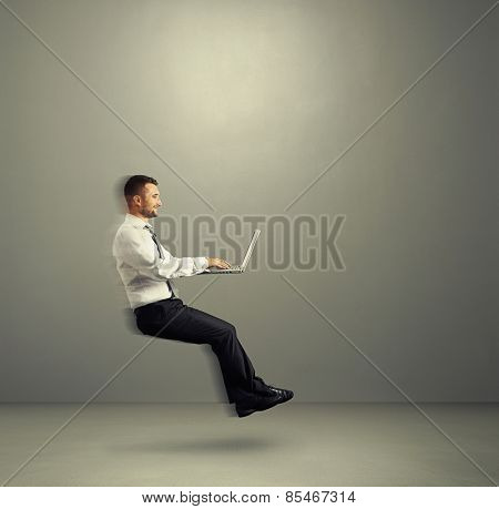 smiley man working with laptop and flying in grey empty room