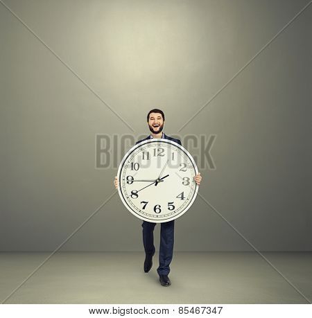 laughing businessman with big clock going forward over grey background