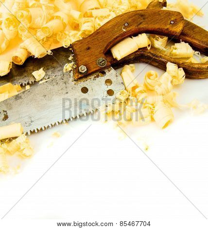 Joiner's works. Wooden shaving and saw on white background.