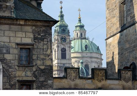 Saint Nicholas Cathedral Between Towers Of Charles Bridge In Prague.
